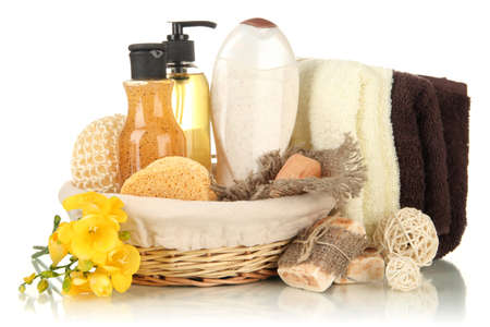 Composition of cosmetic bottles and soap in basket, isolated on white photo