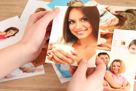 Photos in hands on wooden table photo