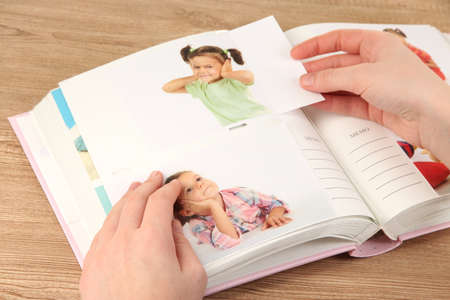 Photos in hands and photo album on wooden table photo