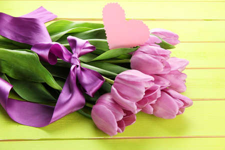 Beautiful bouquet of purple tulips on green wooden background photo