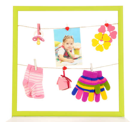 Colorful frame with different things on rope isolated on white photo