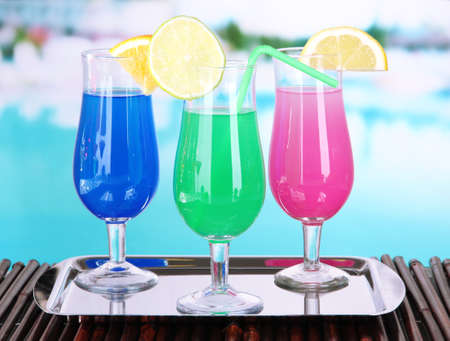 blue hawaiian drink: Glasses of cocktails on table near pool