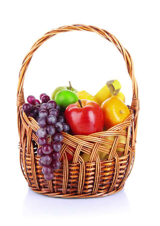 Different fruits in wicker basket isolated on white photo