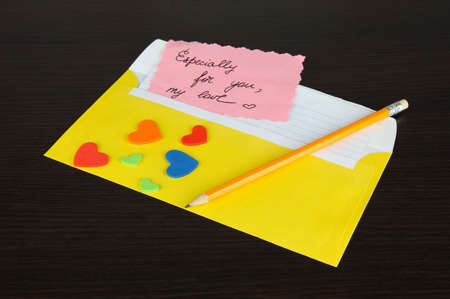 Note in envelope with pencil on wooden background photo