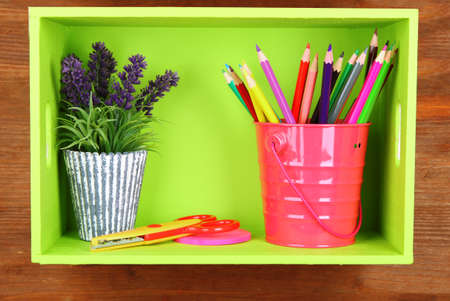 Colorful pencils in pail on shelf on wooden background photo