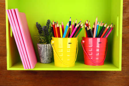 Colorful pencils in pails on shelf with copybooks on wooden background Stock Photo - 18317751