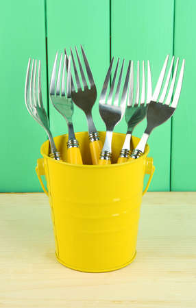 Forks in metal bucket on color wooden background Stock Photo - 18317612
