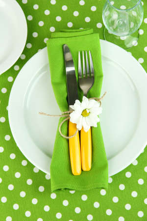 Knife and fork wrapped in napkin, on plate, on color tablecloth  background Stock Photo - 18317728