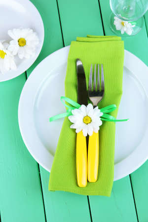 Knife and fork wrapped in napkin, on plate, on color wooden background photo