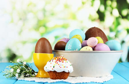 Composition of Easter and chocolate eggs on wooden table on natural background photo