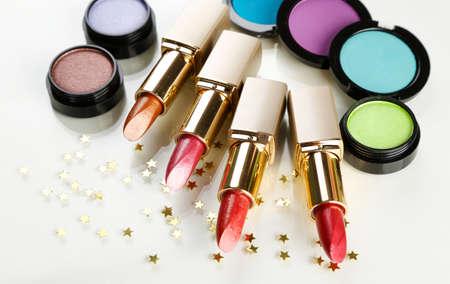 Beautiful lipsticks and eye shadows isolated on white photo