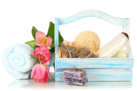 Composition of cosmetic bottles and soap in wooden basket, isolated on white photo