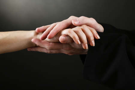 promise: Priest holding woman hand, on black background Stock Photo