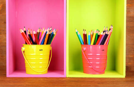 Colorful pencils in pails on shelves on wooden background Stock Photo - 18322981