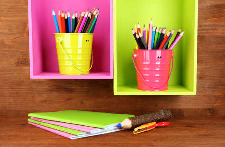 Colorful pencils in pails on shelves on wooden background Stock Photo - 18323389