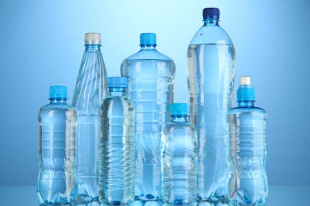 Different water bottles on blue background photo