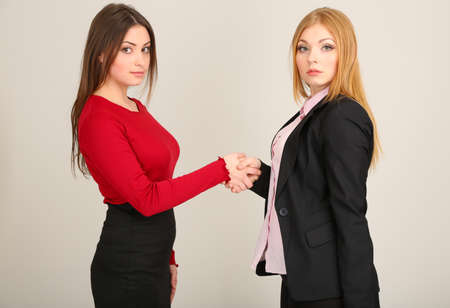 Two business women on grey background photo