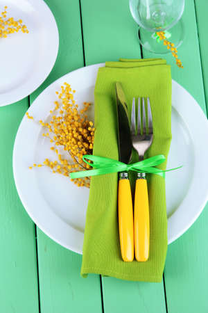 Knife and fork wrapped in napkin, on plate, on color wooden background Stock Photo - 18323471