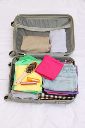 belongings: Open grey suitcase with clothing on bed