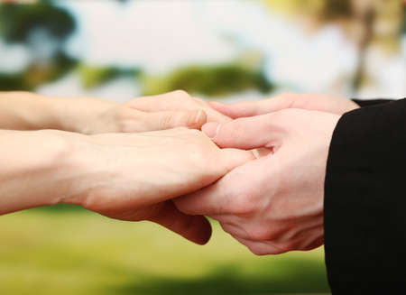 christian women: Priest holding woman hands, on green background