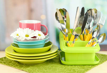 Plates, forks, knives, spoons and other kitchen utensil on color napkin, on bright background Stock Photo - 18323050