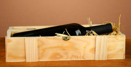 Wine bottle in wooden box on wooden table on brown background photo