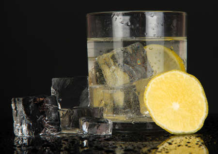 Ice cubes in glass with lemon isolated on black Stock Photo - 18472742