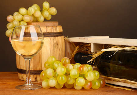Wooden case with wine bottle, barrel, wineglass and grape on wooden table on brown background Stock Photo - 18472828