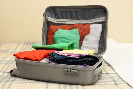 Open grey suitcase with clothing on bed photo