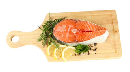 Fresh salmon steak on cutting board, isolated on white photo