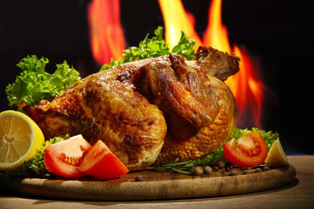 Whole roasted chicken with vegetables on plate, on flame background