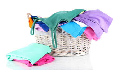 Clothes in wooden basket isolated on white photo