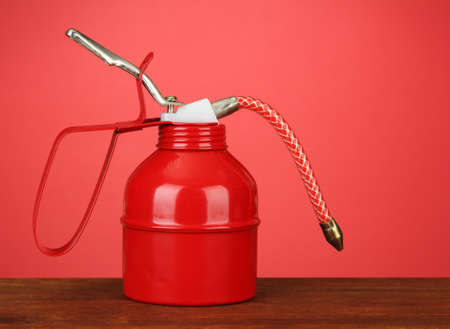 Oil can on red background Stock Photo - 18472707