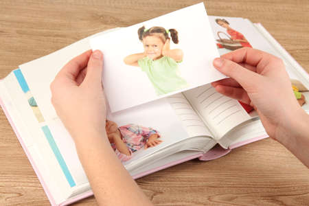 Photos in hands and photo album on wooden table Stock Photo - 19359695