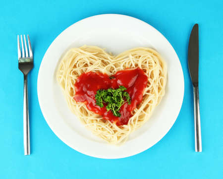 Cooked spaghetti carefully arranged in  heart shape and topped with tomato sauce, on color background photo