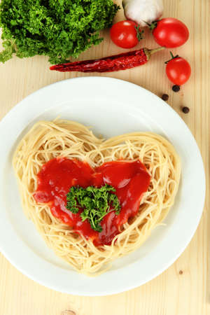 carefully: Cooked spaghetti carefully arranged in  heart shape and topped with tomato sauce, on  wooden background