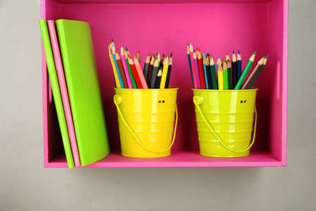 Colorful pencils in pails on shelf on beige background photo