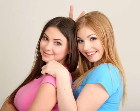 Two girl friends hugging on grey background Stok Fotoğraf