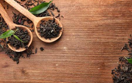 teepflanze: Dry Tee mit gr�nen Bl�ttern in Holzl�ffel, auf Holzuntergrund