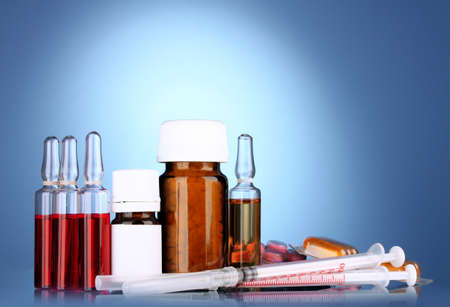 medical ampules, bottles, pills and syringes on blue background photo