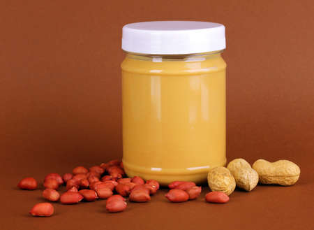 Delicious peanut butter in jar of peanut near on brown background photo