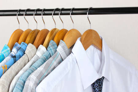 Shirts with ties on wooden hangers on light background photo