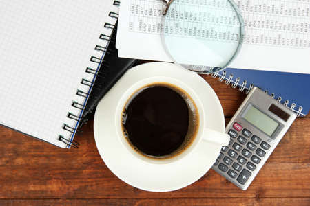 worktable: Cup of coffee on worktable covered with documents close up Stock Photo