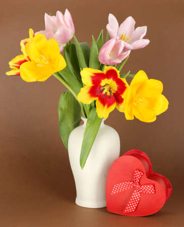 Beautiful tulips in bucket with gift on brown background photo