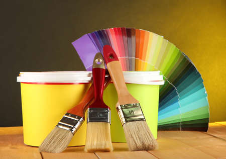 refurbishing: Paint pots, paintbrushes and coloured swatches on wooden table on dark yellow background