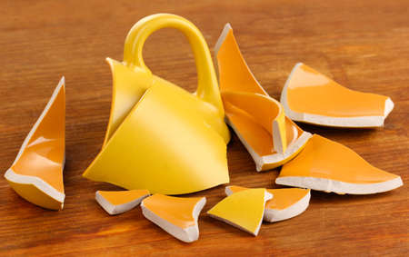 unnecessary: Yellow broken cup on wooden background