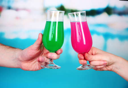 Cocktails in men's and women's hands on pool background Stock Photo - 18574318