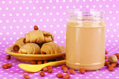 Delicious peanut butter with cookies on purple background with polka dots photo