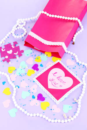 Beautiful composition of paper valentines and decorations on purple background close-up photo