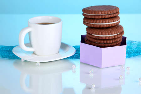 Chocolate cookies with creamy layer and cup of coffe on blue background photo